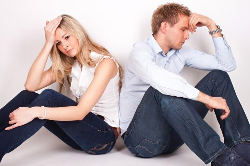 Женщина и мужчина сидят спинами друг к другу